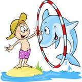 Barn som spelar med delfin Arkivbild