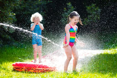 Barn som spelar med den trädgårds- vattenglidbanan royaltyfri fotografi