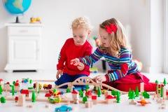 Barn som spelar med det leksakjärnväg och drevet Arkivbild