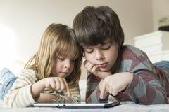 Barn som spelar med en digital minnestavla arkivbilder