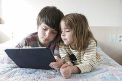 Barn som spelar med en digital minnestavla arkivfoto