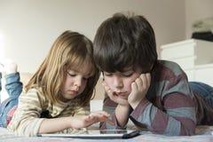 Barn som spelar med en digital minnestavla arkivfoton