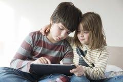 Barn som spelar med en digital minnestavla royaltyfri foto