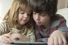 Barn som spelar med en digital minnestavla arkivbild