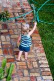 Barn som spelar med en slang arkivbild