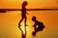 Barn som spelar med gyckel på solnedgånghavsstranden royaltyfria bilder