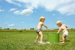 Barn som spelar med hinken av bubblor Arkivfoto