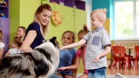 Barn som spelar med hunden under terapi arkivfilmer