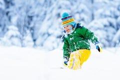 Barn som spelar med insnöad vinter ungar utomhus royaltyfria foton