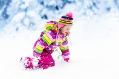 Barn som spelar med insnöad vinter ungar utomhus arkivbilder