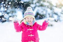Barn som spelar med insnöad vinter ungar utomhus Arkivfoton