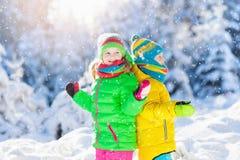 Barn som spelar med insnöad vinter ungar utomhus royaltyfri foto