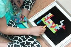 Barn som spelar med kvarter på golvet Arkivfoton