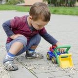 Barn som spelar med leksakbilen Arkivbild
