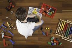 Barn som spelar med leksaker, medan sitta på trägolv Top beskådar royaltyfria foton