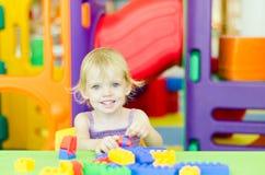 Barn som spelar med ljusa plast- konstruktionskvarter Arkivfoto