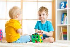 Barn som spelar med logiska bildande leksaker, ordnar och sorterar former eller format Arkivbilder