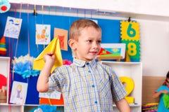 Barn som spelar med origamiflygplanet i grundskola för barn mellan 5 och 11 år Arkivfoton