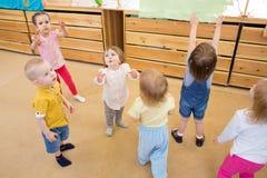 Barn som spelar med såpbubblor i dagis Arkivbild