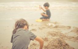 Barn som spelar med sand på stranden Arkivfoton