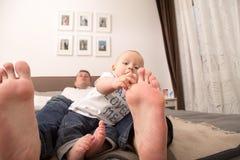 Barn som spelar med stortån av hans fader arkivfoto