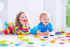 Barn som spelar med träleksaker Arkivfoto