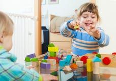 Barn som spelar med träkvarter Arkivbild