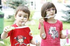 Barn som spelar med tvålballonger Royaltyfria Bilder
