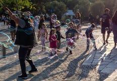 Barn som spelar med tvålbubles i ljuset av solnedgången royaltyfri bild