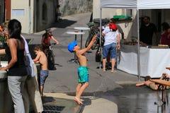 Barn som spelar med vatten under varm dag i lilla staden av Grandvaux, Bourg-en-Lavaux, Schweiz Arkivbild