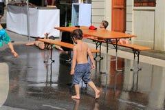 Barn som spelar med vatten under varm dag i lilla staden av Grandvaux, Bourg-en-Lavaux, Schweiz Arkivfoto