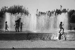 Barn som spelar med vattenstrålar i springbrunnen arkivfoto