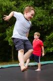 Barn som spelar, medan hoppa på trampolinen utomhus royaltyfri foto