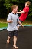 Barn som spelar, medan hoppa på trampolinen utomhus royaltyfri bild