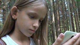 Barn som spelar minnestavlan som är utomhus-, i att campa, ungebrukssmartphone, borttappad flicka i skog stock video