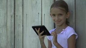 Barn som spelar minnestavlan av staketflickan som använder utomhus- barn för smartphone som studerar 4K arkivfilmer