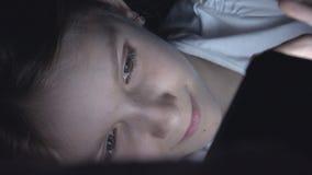 Barn som spelar minnestavlan i m?rk natt, flicka som bl?ddrar internet i s?ng som inte sover arkivfoto