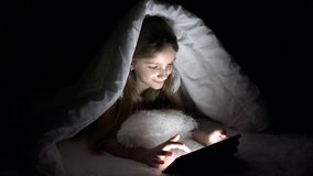 Barn som spelar minnestavlan i m?rk natt, flicka som bl?ddrar internet i s?ng som inte sover stock video