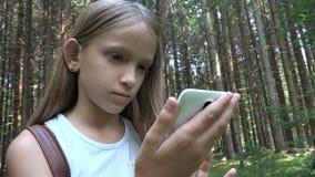 Barn som spelar minnestavlan som ?r utomhus-, i att campa, ungebruk Smartphone i skogen, flickasikt arkivbilder