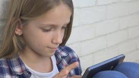 Barn som spelar minnestavlan, unge Smartphone, flickaläsningmeddelanden som bläddrar internet stock video
