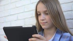 Barn som spelar minnestavlan, unge Smartphone, flickal?sningmeddelanden som bl?ddrar internet royaltyfria foton