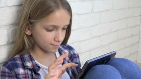 Barn som spelar minnestavlan, unge Smartphone, flickal?sningmeddelanden som bl?ddrar internet lager videofilmer