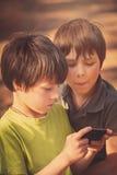 Barn som spelar mobiltelefonen utomhus Arkivfoto