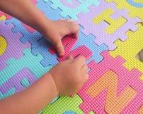 Barn som spelar och lär bokstäver med färgrika pussel Royaltyfria Foton