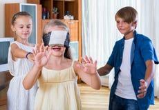 Barn som spelar på bluffen för blind man inomhus arkivbild