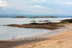 Barn som spelar på de svarta sanderna, sätter på land i Aberdour i Skottland Royaltyfri Bild
