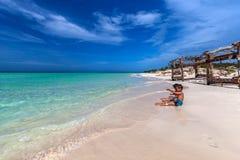 Barn som spelar på den vita sandiga kubanska stranden i den Cayo cocoen Arkivfoto