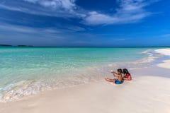 Barn som spelar på den vita sandiga kubanska stranden i den Cayo cocoen Arkivfoton