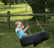 Barn som spelar på en gummihjulgunga Royaltyfri Bild