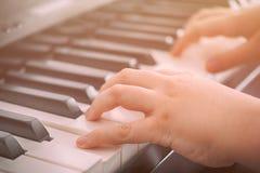 Barn som spelar på ett digitalt piano Arkivfoton